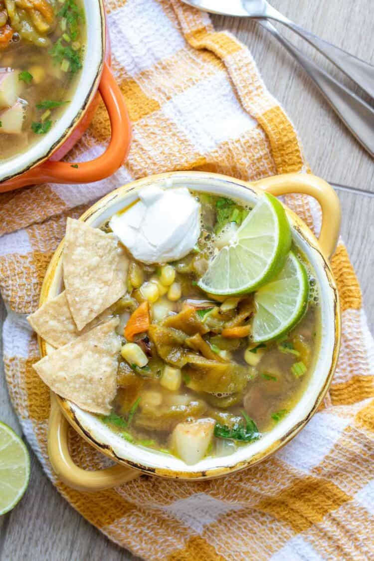 A broth based soup with corn, potatoes and peppers topped with lime, sour cream and chips