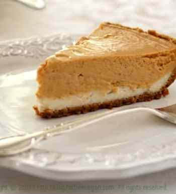 vegan pumpkin cheesecake on white plate with silver fork holiday table thanksgiving dessert