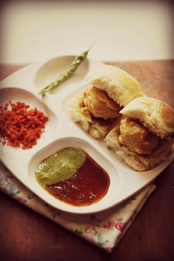 vada pav with green chilies, garlic chutney, green chutney and sweet chutney