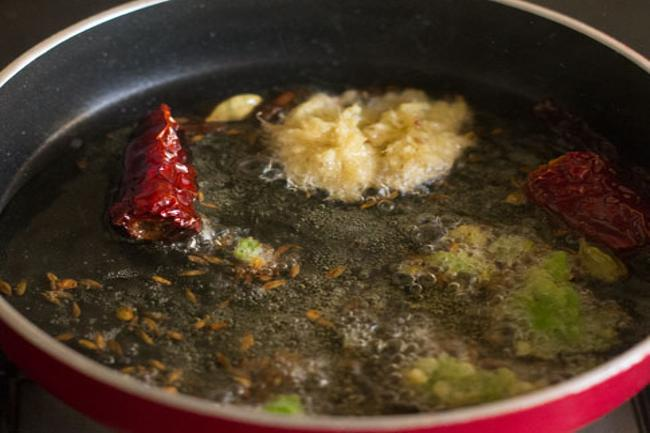adding crushed ginger and green chili