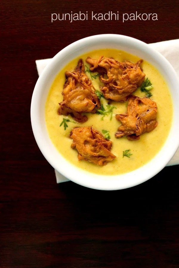 kadhi topped with pakora and coriander leaves served in a white bowl