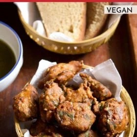 palak pakoda served in a bowl with a side of wheat bread slices and coriander chutney on a wooden board