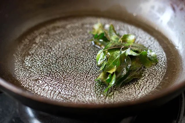 sautéing curry leaves in a pan