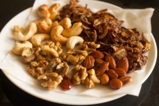 fried walnuts placed on paper towel with other garnishes for kashmiri pulao