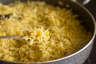 fluffing completed Kashmiri pulao recipe with a fork