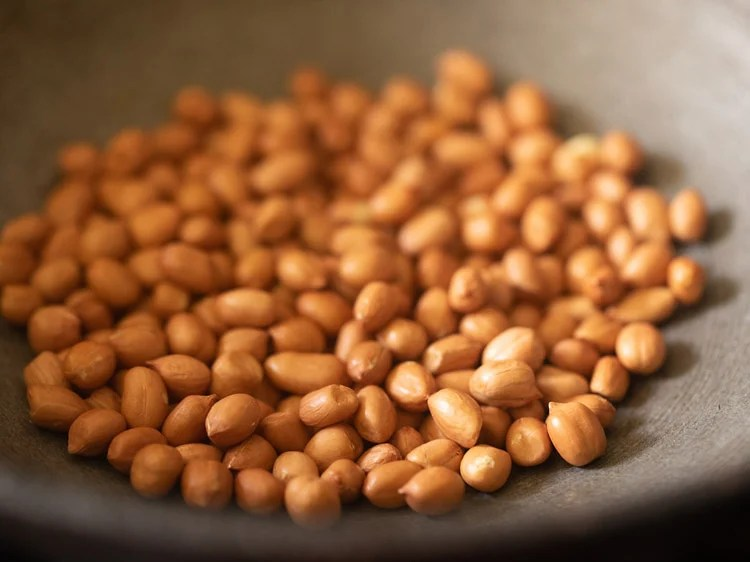 adding peanuts in a frying pan