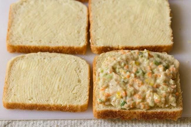 adding coleslaw stuffing on bread slice