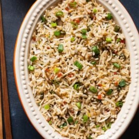fried rice in a oval ceramic bowl with wooden chopsticks at side on a slate black board