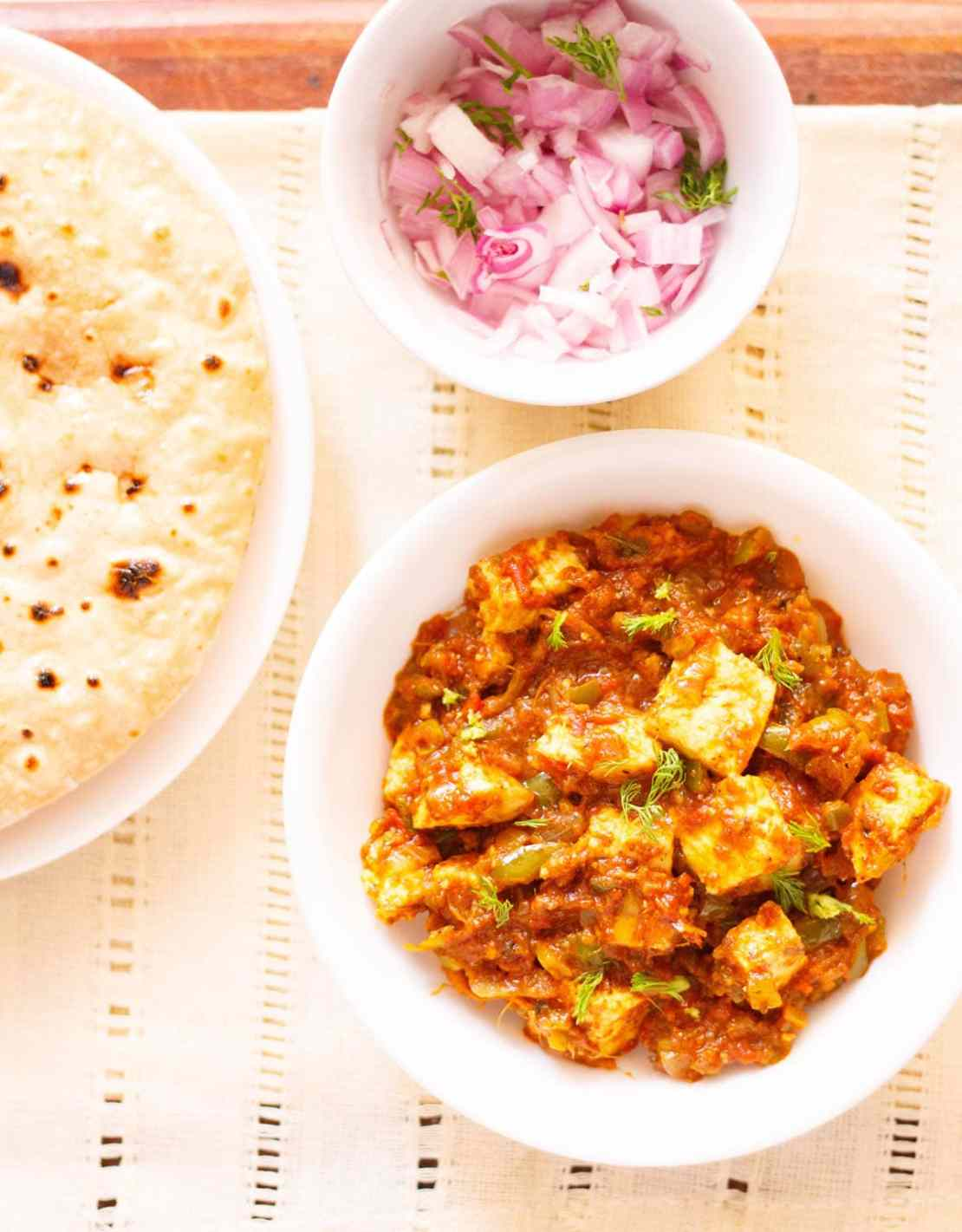 overhead shot of tawa paneer with coriander leaves garnish in a white bowl on a cream linen with a side plate of roti and a small side bowl of chopped red onions and coriander leaves