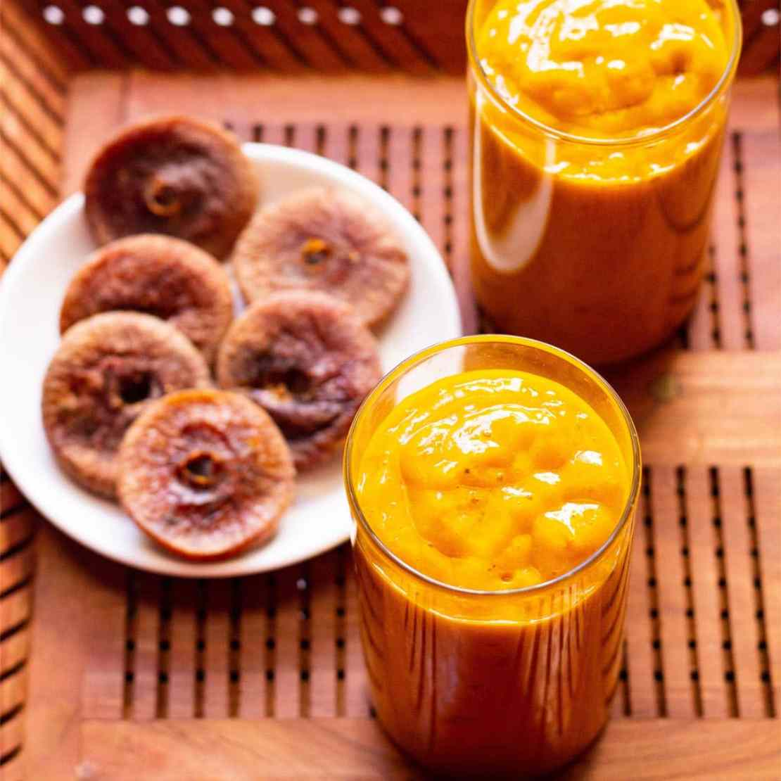 mango smoothie with figs served in two glasses and a white plate of dried figs on a wooden tray