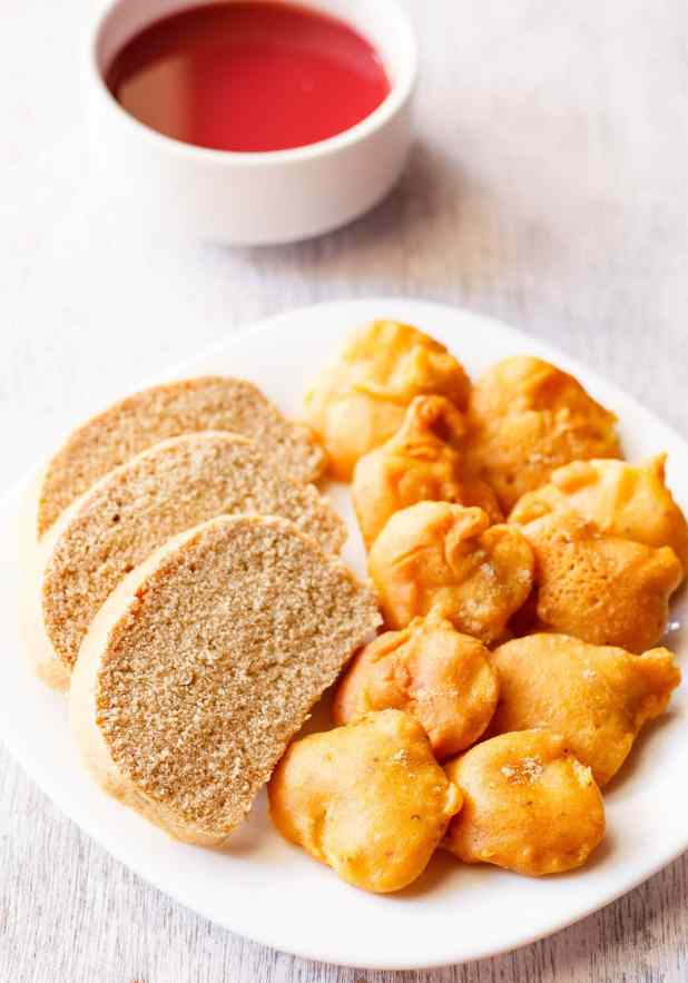closeup shot of aloo pakora arranged on a plate with slices of wheat bread on a square white plate