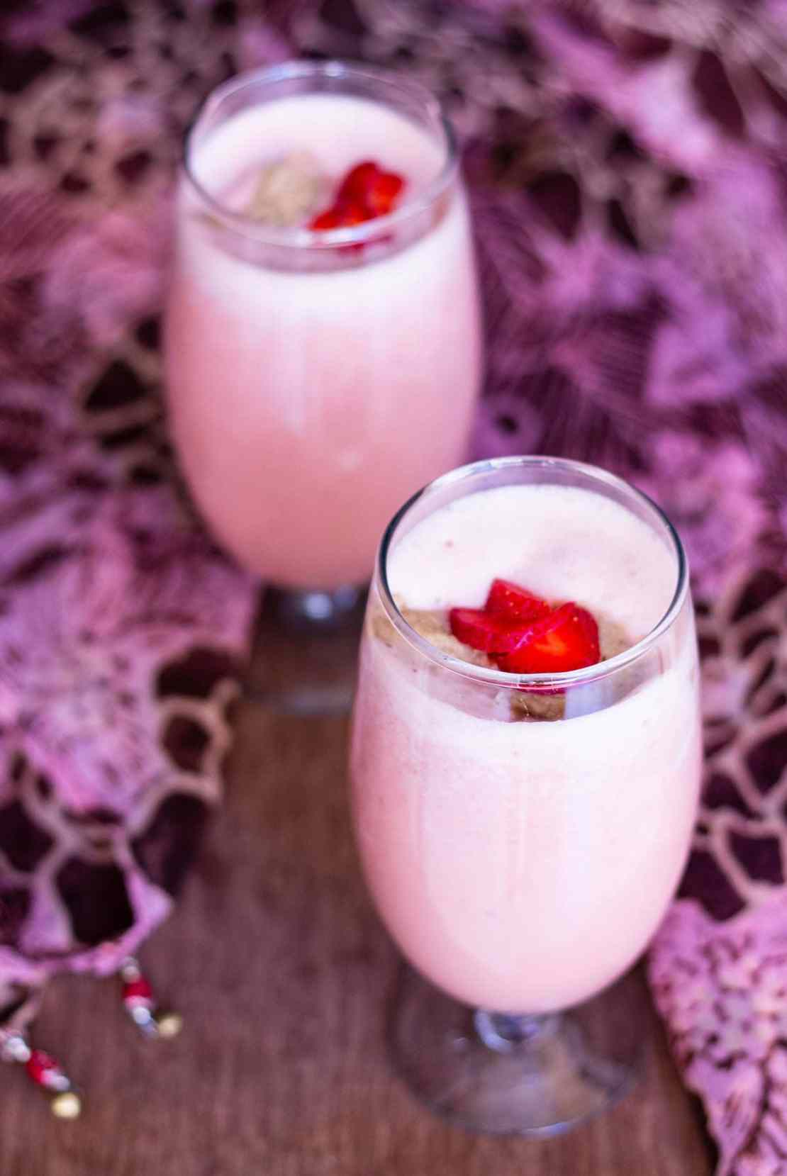 two glasses of vegan strawberry shake topped with strawberry slices and ice cream with a pink and brown fabric around on a wooden board