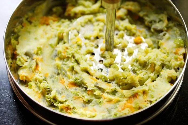 mashing veggies with a potato masher