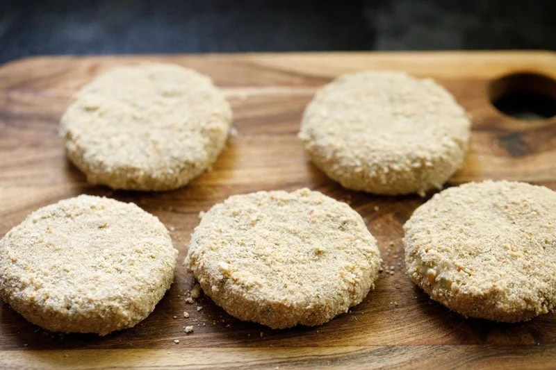 crumb coated cutlets on wooden board