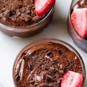 overhead shot of three bowls of chocolate mousse topped with grated chocolate and a strawberry halve in a glass bowl on a white marble board with text layovers