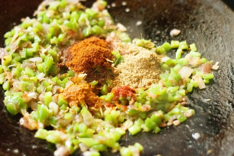 ground spices on capsicum and onion mixture