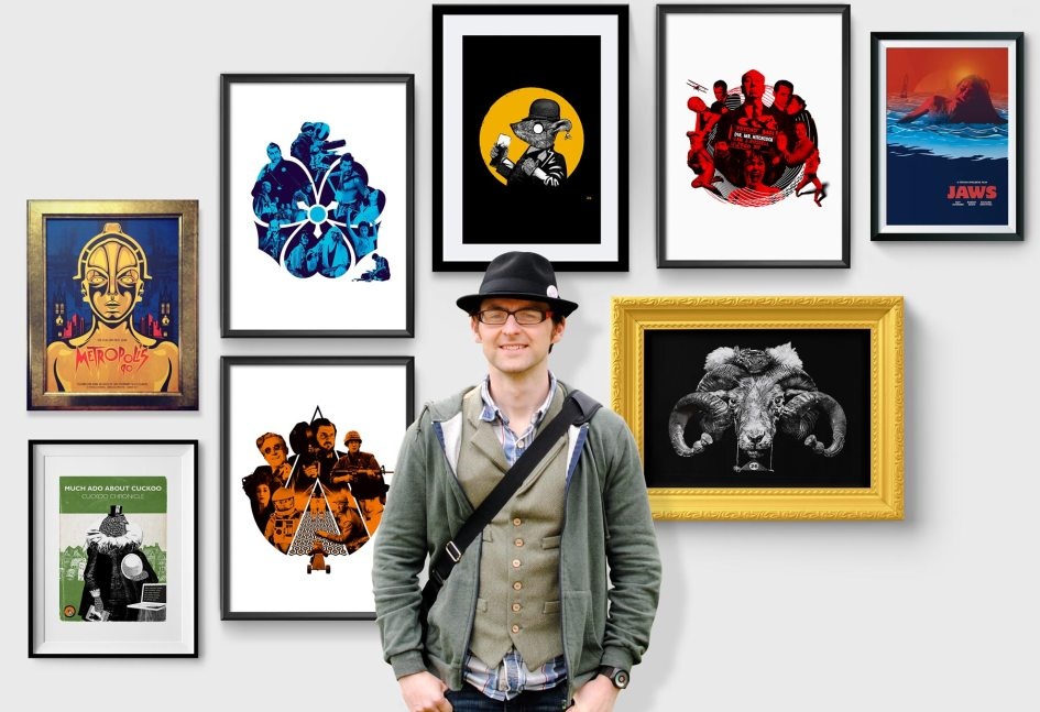 David McClure stands in front of framed artworks