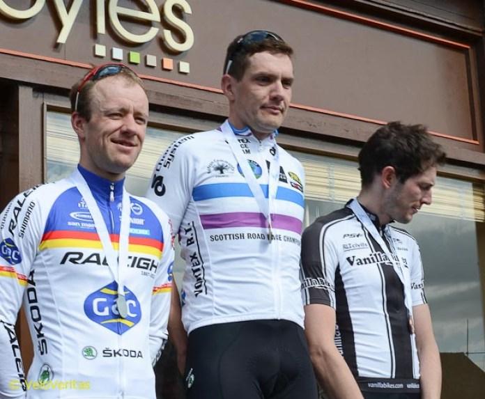 The men's podium, Evan second, winner James sports the winner's jersey, and Alistair third.
