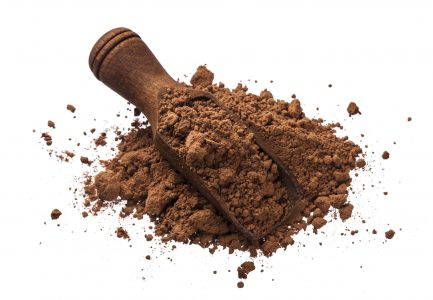Pile of cocoa powder isolated on white background with clipping path, cinnamon powder in wooden scoop