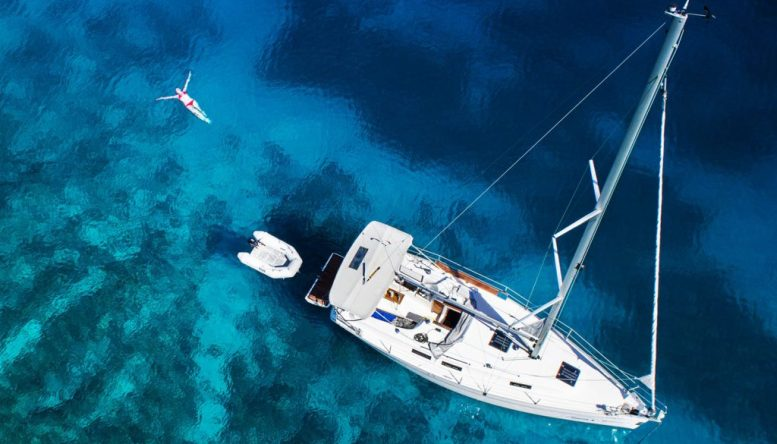 amazing view to yacht, swimming woman and clear water - caribbean paradise
