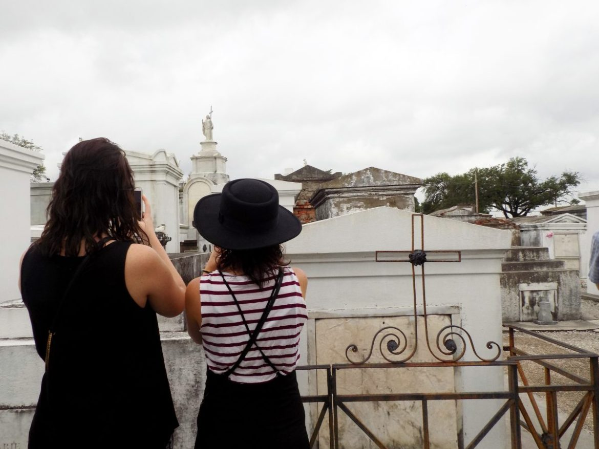 Two women taking pictures of the catacombs in New Orleans on a tour. Joining a tour is a great way to make new friends while solo traveling.