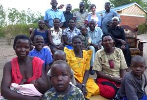På gruppbilden ser vi ,från vänster längst bak,  Boniface Gum, Lino Kehmis, Isaac Olobo, Matilda Utbult från Sverige, och. Ponsiano Okalo. I mitten  sitter Janet Akello, Brenda Ajangi, Palma Atoke, pojken Sheriffa, Angelos Kula och Amina Delino. Längs fram sitter Hariet Gum, Dunlas Atepo, Jacinta Awor och Nightie Ocengum –  tilllsammans med några barn. I bakgrunden ett nybyggt gemensamt byhus.
