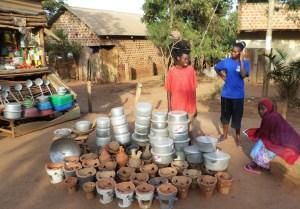 Miljonstaden Kampala växer snabbt ut åt alla håll och här kan man bokstavligen se medelklassens tillväxt genom de välbyggda och stabila tegelhus som byggs, inte stora men rejäla.  På ett litet torg här i förorten Kumunana säljer unga kvinnor köksredskap, inklusive de koleldade minispisarna i keramik. (Foto: Daniel van der Blij)