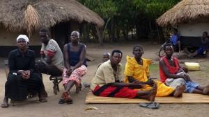 På bilden från mötet, med hyddor för matlagning i bakgrunden, sitter från vänster Amina Delino, Isaac Olobo, Janet Akello, Hariet Gum, Jacinta Awor och Nightie Ocengum.