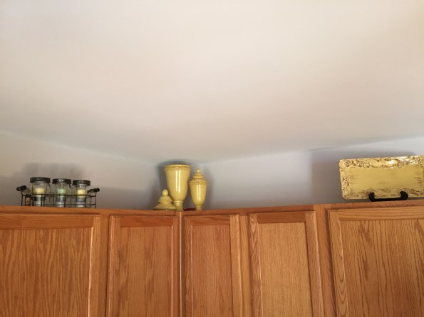 Right corner of the cabinets showing my mason jar candle holders, gold canisters and gold platter