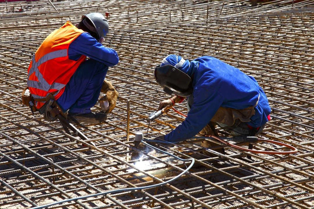 Two construction workers working