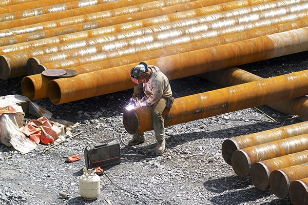 Construction Worker Sitting on Pipe