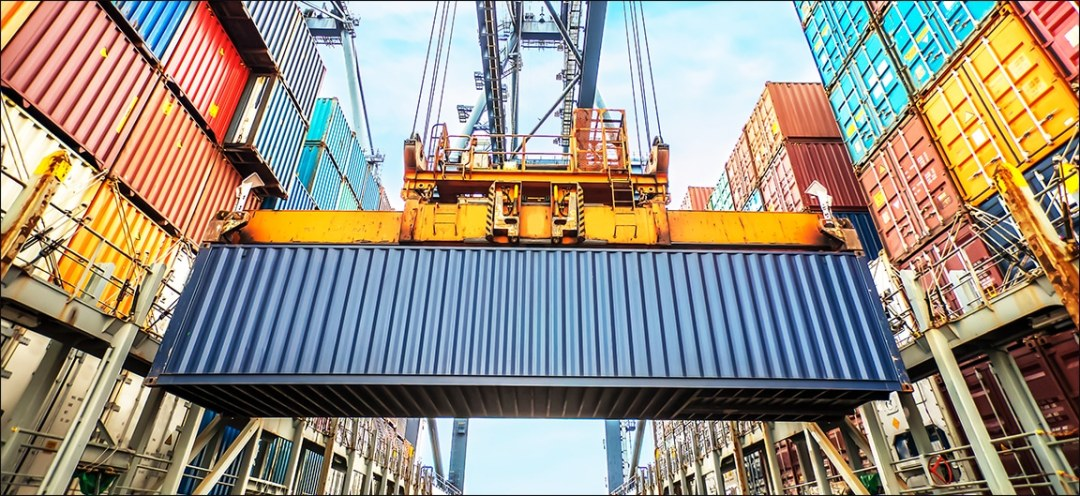 Crane lifting shipping container at port