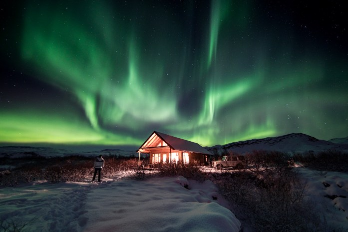 Northern lights above a building in Iceland
