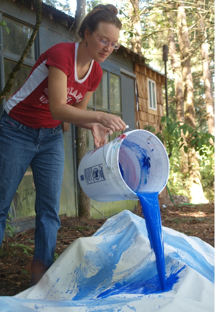 Veronica Reeves pouring paint on raw canvas supported by branches.