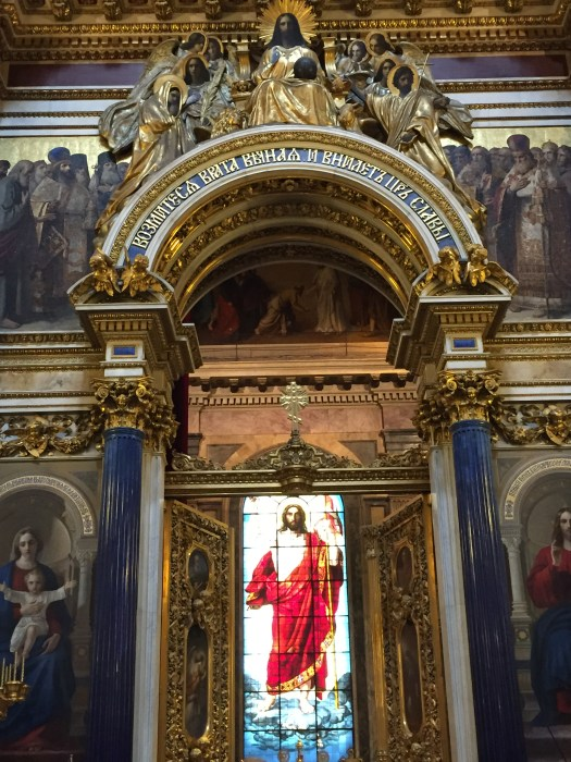 """A large, brightly coloured stained glass window of the """"Resurrected Christ"""" inside the main altar of St. Isaac's Cathedral, St Petersburg."""