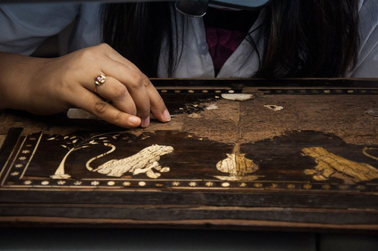 Grime and old adhesive are being cleaned from the ivory-inlaid teak wood surface of an indo-portuguese fall-front cabinet from Gujarat/Sindh (C. 17th century)