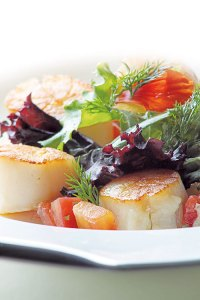 Pan seared scallops with organic leaves and tomatoes