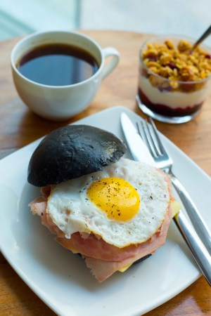 Light brioche sandwich eggs cheese and ham with coffee and berry and granola yogurt