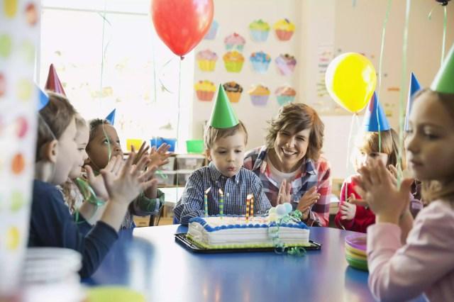 Teacher and children celebrating birthday in school