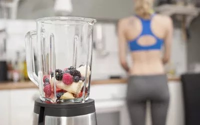 Mixer with fruits in the kitchen with young woman in the background, Bavaria, Germany