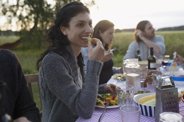 Smiling woman eating and enjoying garden party dinner