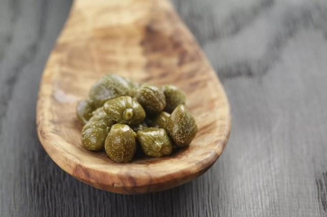 Capers on a wooden spoon