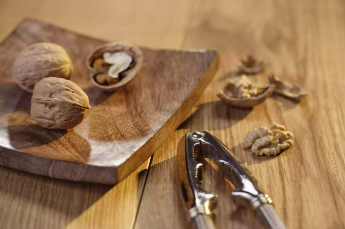Walnut pieces and nutcracker on cutting board, close-up