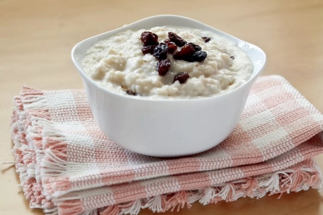 A bowl of oatmeal with raisins on top
