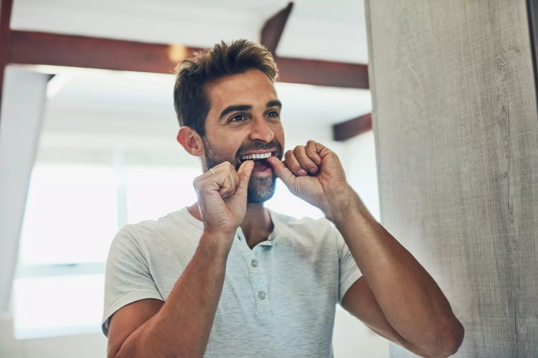 رجل ينظف أسنانه بالخيط