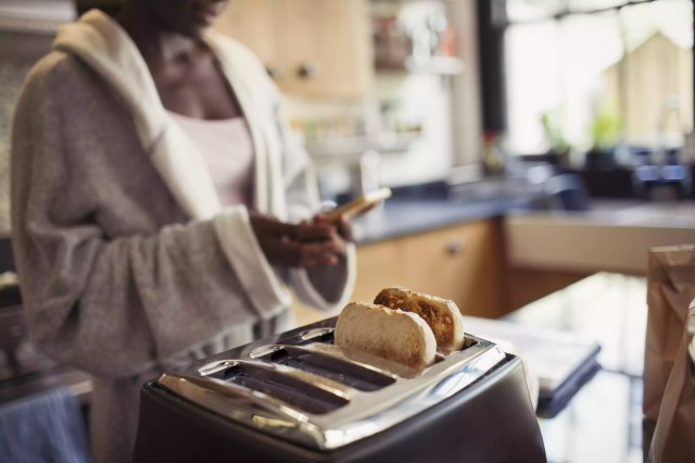 Woman texting with smart phone, toasting bread in toaster in kitchen