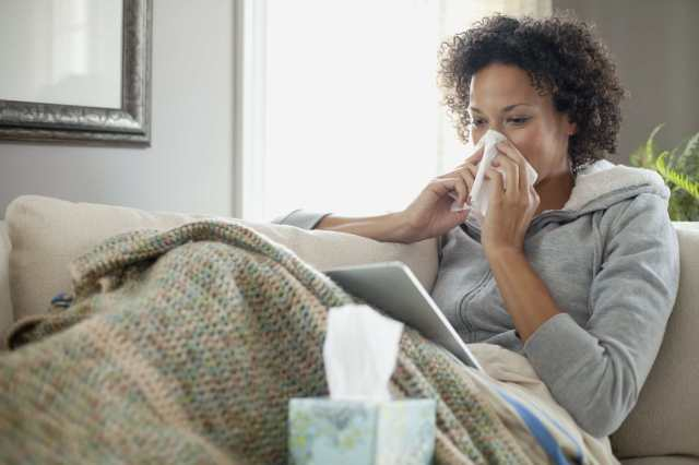 woman nursing a cold at home