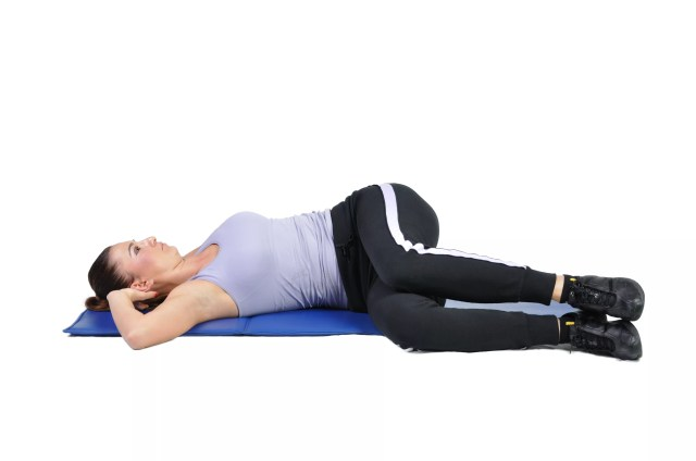 A woman in the supine position twists her spine by bringing her knees to one side.