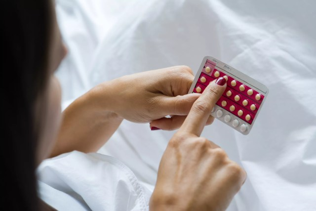 woman holding birth control pill pack