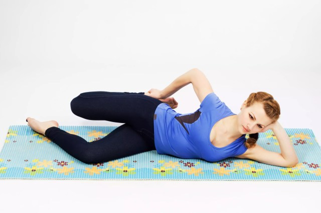 A woman stretches her quadriceps muscles while lying on her side.